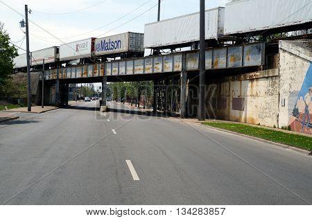 JOLIET, ILLINOIS / UNITED STATES - MAY 3, 2015: A freight train crosses a bridge over Scott Street near downtown Joliet, Illinois.