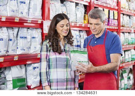 Salesman Assisting Customer In Buying Pet Food At Store poster