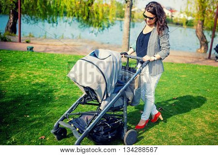Elegant Mother Smiling With Baby In Park. Mother Walking Child With Pram Or Baby Stroller