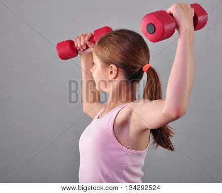 Teenage sportive girl is doing exercises to develop muscles isolated on grey background. Sport healthy lifestyle concept. Sporty childhood. Teenager exercising with wieghts.