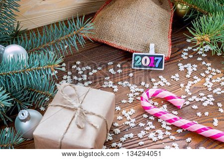 christmas gifts packaged in craft paper and black nameplate with colorful wood new year numbers pink candy cane sprinkling as snowflakes on wooden table.