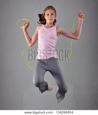 Healthy young muscular teenage girl skipping rope in studio. Child exercising with jumping on grey background.