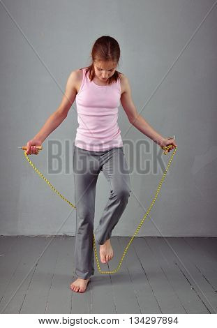 Healthy young muscular teenage girl skipping rope in studio. Child exercising with jumping high on grey background. Sport healthy lifestyle concept. Sporty childhood. poster