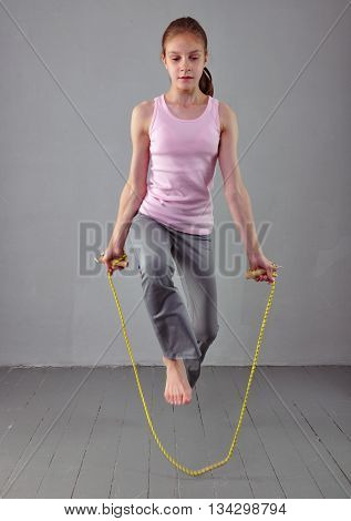Healthy young muscular teenage girl skipping rope in studio. Child exercising with jumping on grey background. Sport healthy lifestyle concept. Sporty childhood.
