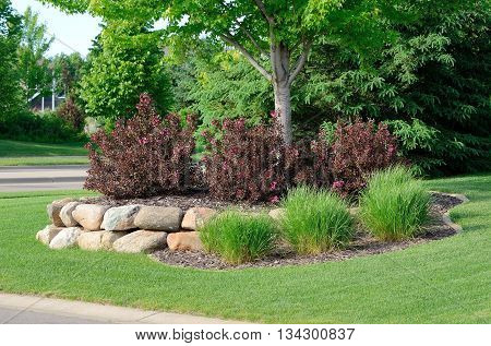 Landscaping with Weigela Shrubs and Rock Retaining Wall at a Residential Home