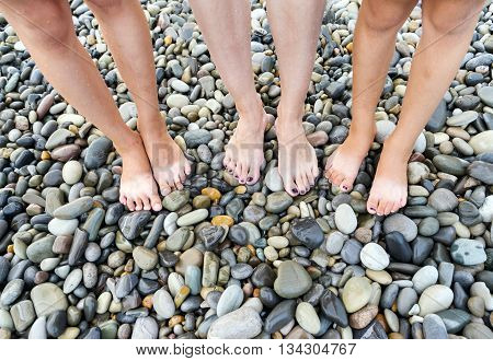 Wet feet of mother and small children's on beach the sea in a summer sunny day. Family holiday