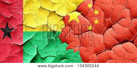Guinea bissau flag with China flag on a grunge cracked wall