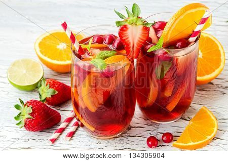 Cranberry drink homemade lemonade or sangria with citrus fruits and berries on white background refreshing cocktail for hot summer days