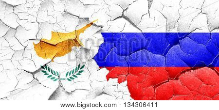 Cyprus flag with Russia flag on a grunge cracked wall