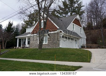 HARBOR SPRINGS, MICHIGAN / UNITED STATES - DECEMBER 24, 2015: A large home with an attached garage, under the bluff on Fourth Street in Harbor Springs, during December.