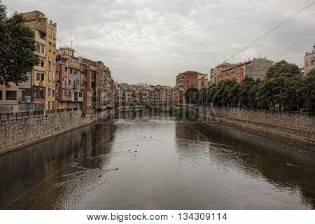 GIRONA SPAIN - JULY 17 2013: Onyar River in Girona. It divides the city into two parts: on the left bank is the historical center on the right - the usual modern Catalan city