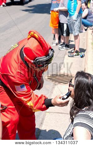 WEST ST. PAUL, MINNESOTA - MAY 21, 2016: 2016 St. Paul Winter Carnival Prince of Soot Emilio Munoz applies face paint on a spectator at annual Grande Parade in West St. Paul on May 21.