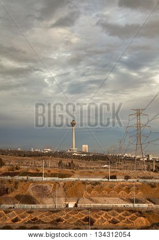 Milad Tower and power transmission lines above hillside against gray overcast sky of Tehran in autumn. poster