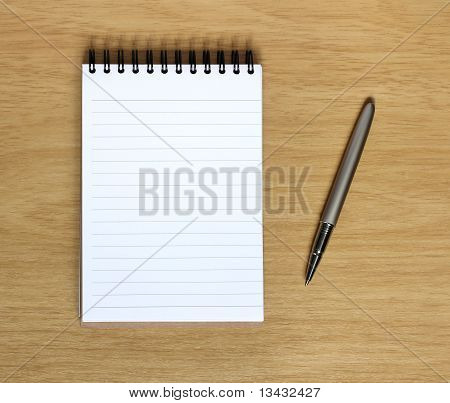 Notebook With Pen On Wooden Desk