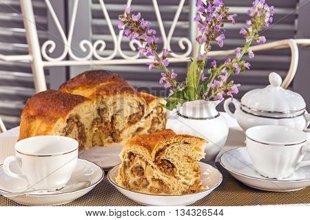 Typical italian flavorous farmhouse cake La Gubana with sophisticated stuffing (hazelnuts fruit chocolate walnut raisins honey etc.) on the table covered for tea time. Traditionally bake for Christmas and Easter.