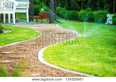 Backyard Residential Garden Grass Field Sprinklers in Action. Garden Path.