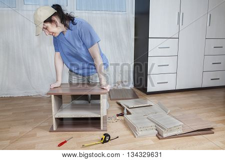 Flat pack furniture woman assembling wooden bedside tables using glue on floor in living room.