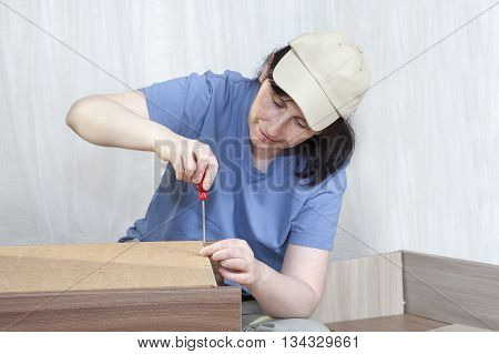 Furniture assemblage at home woman fastens of sheet hardboard to bedside cabinet frame tightening screw with a hand screwdriver.