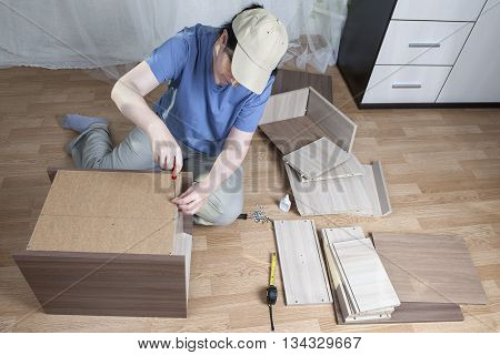 Assembling of furniture at home woman fastens a sheet of hardboard in the back of the nightstand using a hand screwdriver.