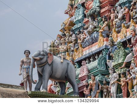 Chettinad India - October 17 2013:Detail of the Shiva temple gopuram at Kottaiyur shows Lord Shiva as supreme teacher and elephant walking away. Plenty of colorful statues.