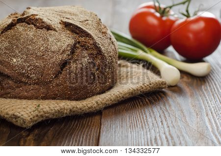 Baked bread with tomatos onion on wooden table background for lunch