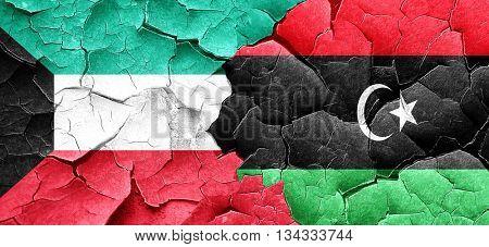 Kuwait flag with Libya flag on a grunge cracked wall