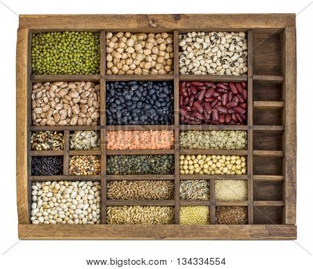 assorted beans, lentils, grains and seeds in an old, wooden typesetter drawer isolated on white
