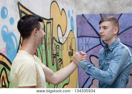 Two teenagers on the street greeting each other with graffiti background