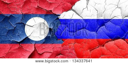 Laos flag with Russia flag on a grunge cracked wall
