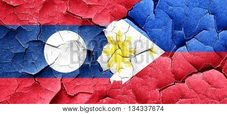 Laos flag with Philippines flag on a grunge cracked wall