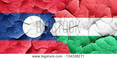 Laos flag with Hungary flag on a grunge cracked wall