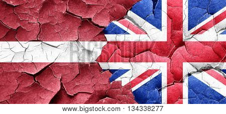 Latvia flag with Great Britain flag on a grunge cracked wall