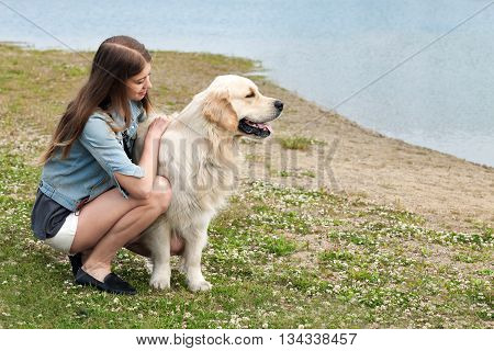 Portrait of a young girl and her dog golden retriever outdoors in the summer. On the bank of the river