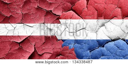 Latvia flag with Netherlands flag on a grunge cracked wall