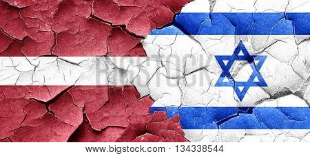 Latvia flag with Israel flag on a grunge cracked wall