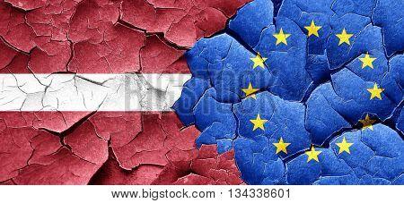 Latvia flag with european union flag on a grunge cracked wall