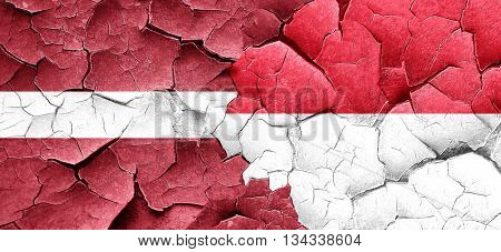 Latvia flag with Indonesia flag on a grunge cracked wall