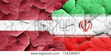 Latvia flag with Iran flag on a grunge cracked wall