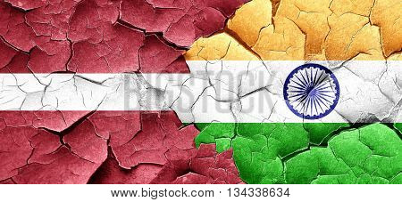 Latvia flag with India flag on a grunge cracked wall