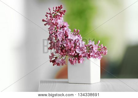 Purple lilac flowers in a vase on blurred background
