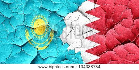 Kazakhstan flag with Bahrain flag on a grunge cracked wall