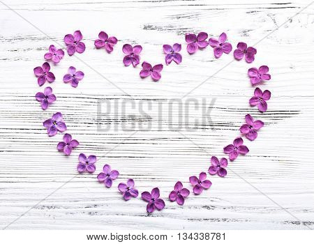 Heart made with lilac flowers on wooden background