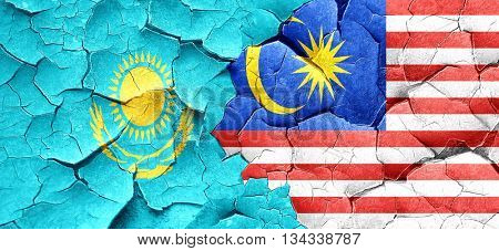 Kazakhstan flag with Malaysia flag on a grunge cracked wall