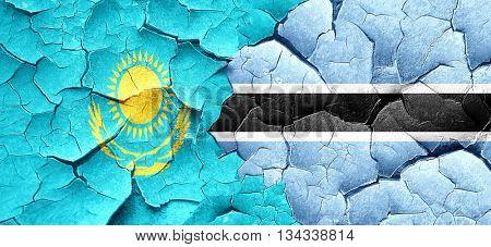 Kazakhstan flag with Botswana flag on a grunge cracked wall