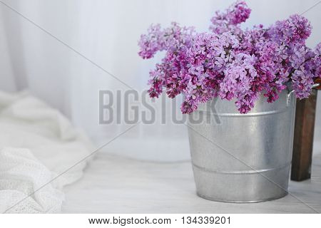 Bouquet of lilac flowers on white wooden floor