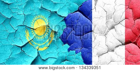 Kazakhstan flag with France flag on a grunge cracked wall