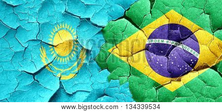 Kazakhstan flag with Brazil flag on a grunge cracked wall