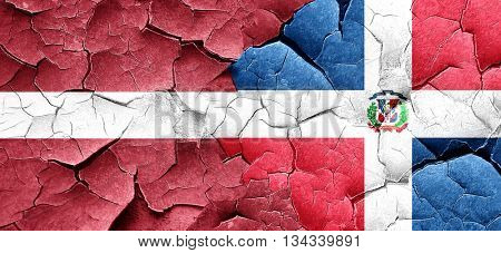 Latvia flag with Dominican Republic flag on a grunge cracked wal