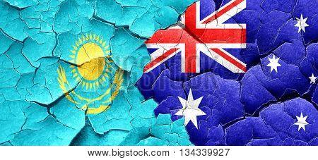 Kazakhstan flag with Australia flag on a grunge cracked wall