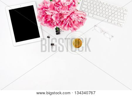 Feminine office workplace with coffee and flowers. Mockup with digital Tablet PC. Flat lay for social media blogger